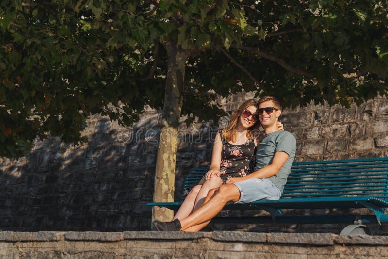 Pares novos no amor assentados em um banco e no relaxamento durante um dia ensolarado imagem de stock