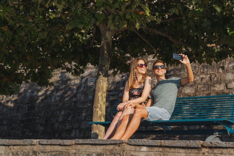Pares novos no amor assentados em um banco que toma um selfie e que relaxa durante um dia ensolarado foto de stock royalty free