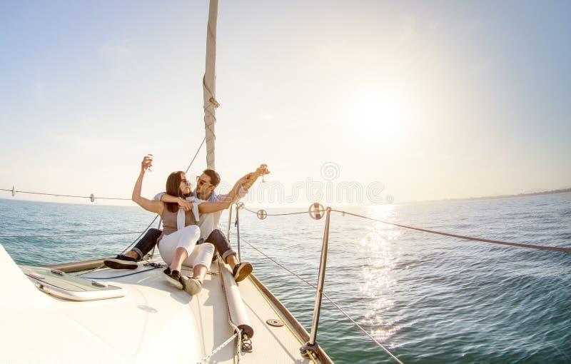 Pares novos no amor no barco de vela com champanhe no por do sol - Hap fotos de stock royalty free