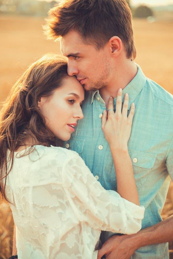 Pares novos no amor exterior Acople o aperto Pares bonitos novos no amor que fica e que beija no campo no por do sol imagens de stock royalty free