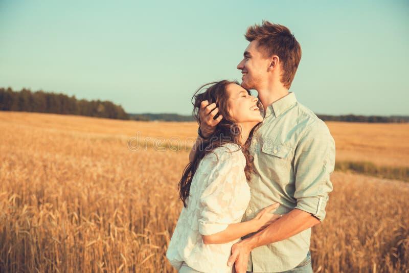 Pares novos no amor exterior Acople o aperto Pares bonitos novos no amor que fica e que beija no campo no por do sol fotografia de stock
