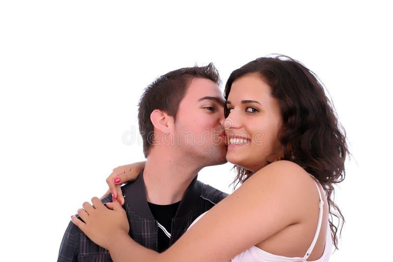 Pares novos no amor, menino que beija a menina imagem de stock royalty free