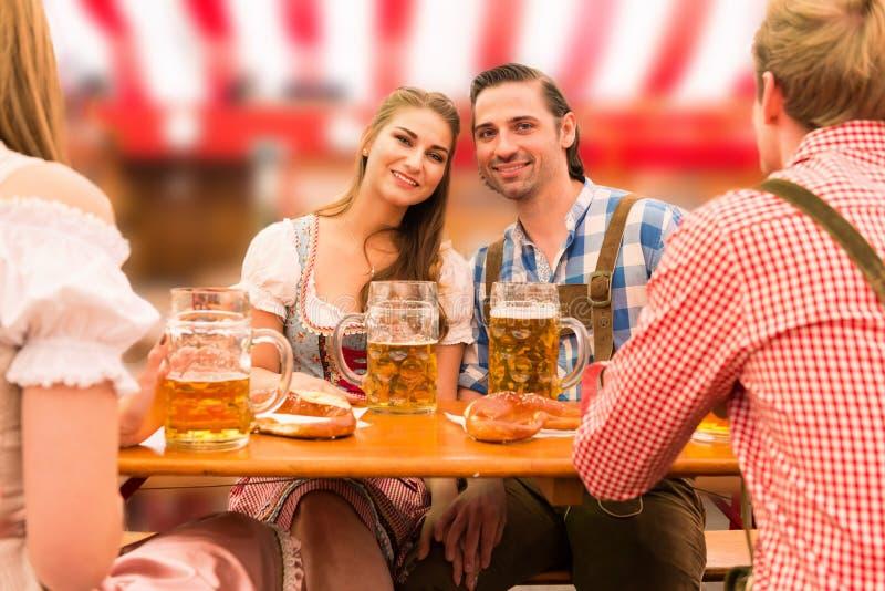 Pares novos no amor na barraca da cerveja de Oktoberfest fotos de stock royalty free