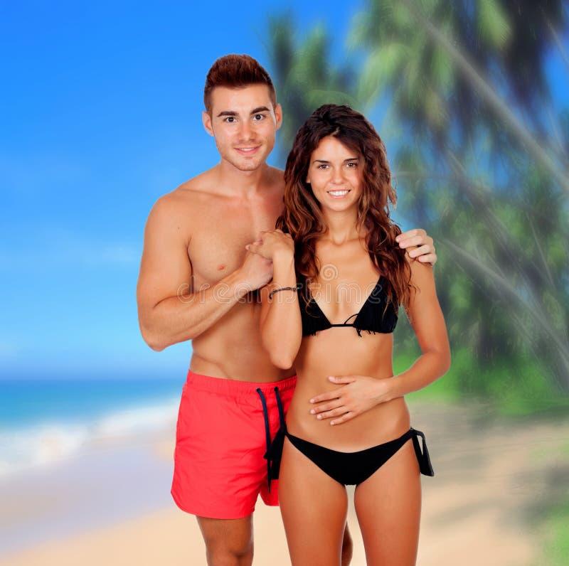 Pares novos no amor na praia imagem de stock