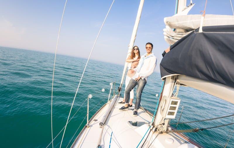 Pares novos no amor no barco de vela que tem o divertimento com champanhe fotografia de stock