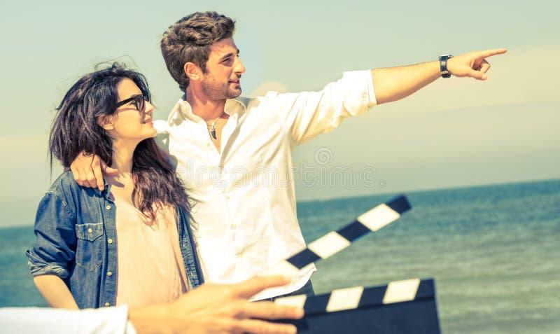Pares novos no amor que actua para o filme romântico na praia imagens de stock