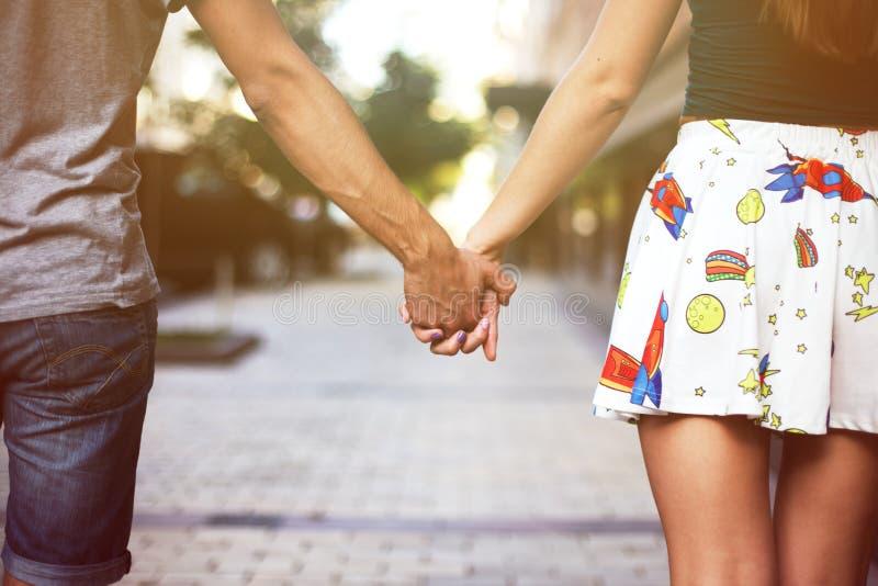 Pares novos no amor que anda no parque que guarda as mãos que olham no por do sol fotografia de stock