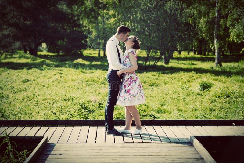 Pares novos no amor que está em estradas transversaas de madeira imagem de stock royalty free