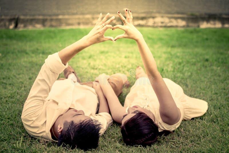 Pares novos no amor que estabelece na grama e que faz a mão no coração foto de stock