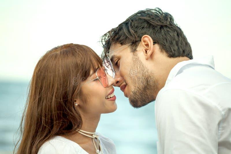 Pares novos no amor que olha entre si e que mantém a mão unida na praia do mar no céu azul casamento novo de sorriso feliz com imagem de stock