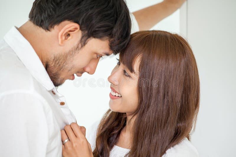 Pares novos no amor que olha entre si marido de ajuda da esposa a conseguir vestir-se acima no momento romântico da manhã imagens de stock