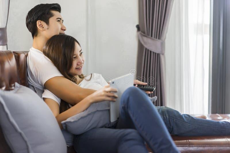 Pares novos no amor que senta-se em um sofá marrom e em um televi de observação fotos de stock