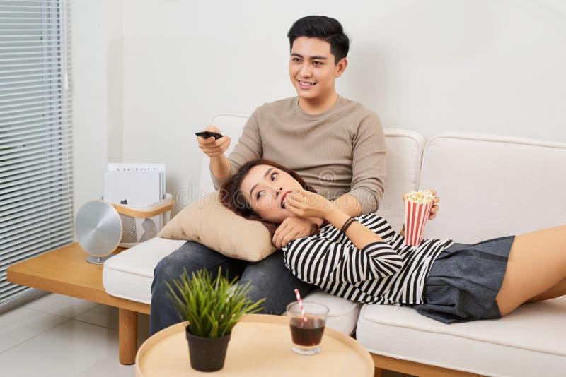 Pares novos no amor que senta-se em um sofá marrom e em um televi de observação imagens de stock royalty free