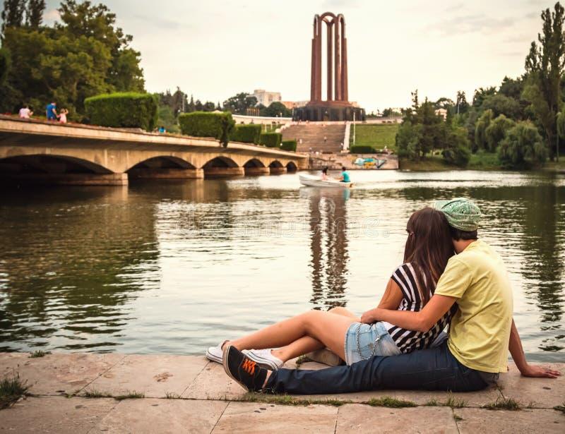Pares novos no amor que senta-se perto do lago na paisagem do parque fotos de stock