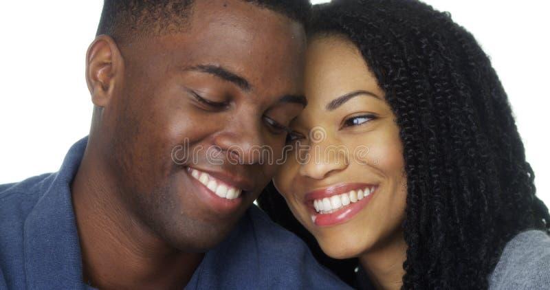 Pares novos no amor que sorri e que olha a câmera imagem de stock