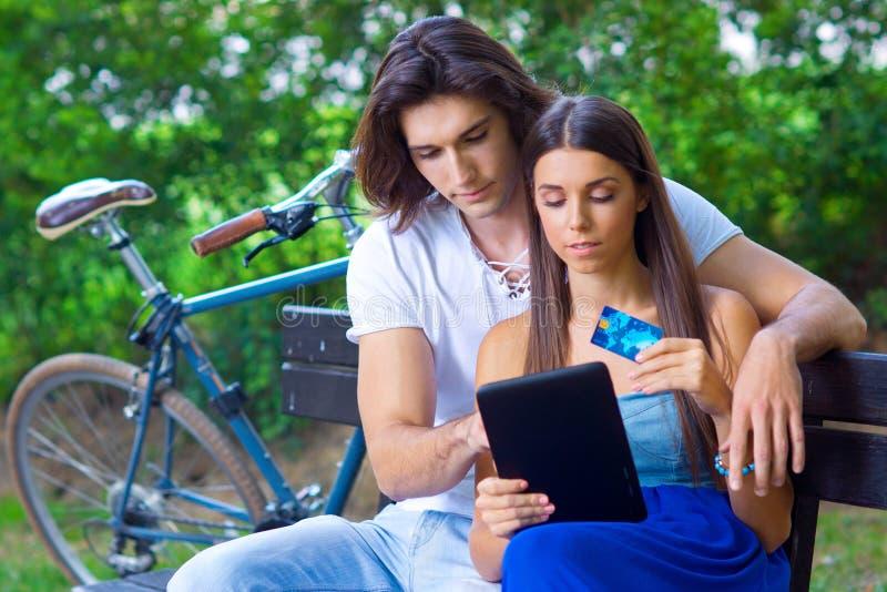 Pares novos no banco de parque com cartão e tabuleta de crédito fotografia de stock