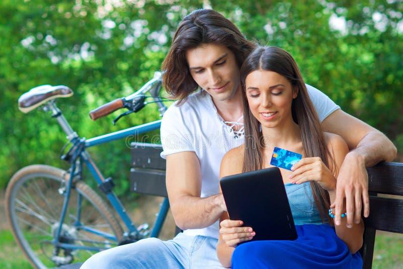Pares novos no banco de parque com cartão e tabuleta de crédito fotografia de stock royalty free