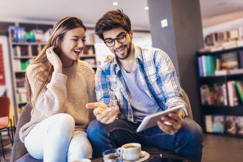 Pares novos no café interno usando a tabuleta digital fotos de stock royalty free