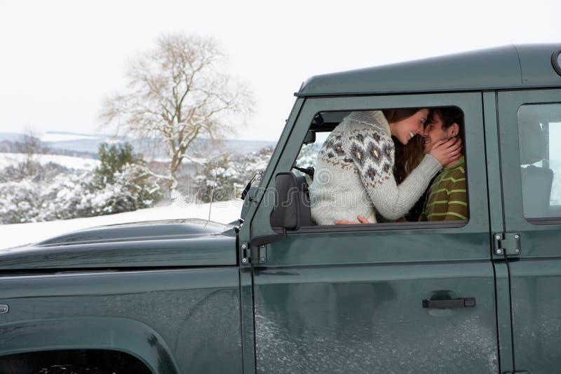 Pares novos no carro na neve fotografia de stock royalty free