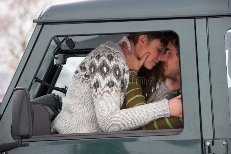 Pares novos no carro na neve foto de stock