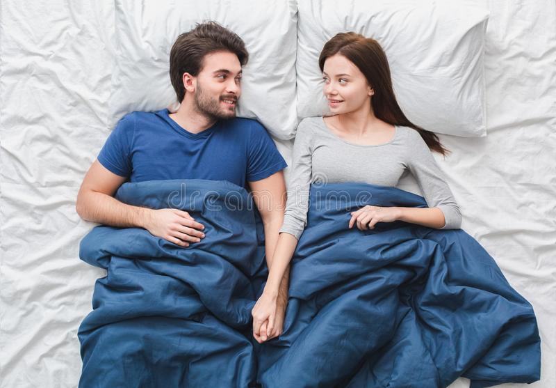 Pares novos no conceito da manhã da opinião superior da cama que guarda o sorriso das mãos imagens de stock royalty free