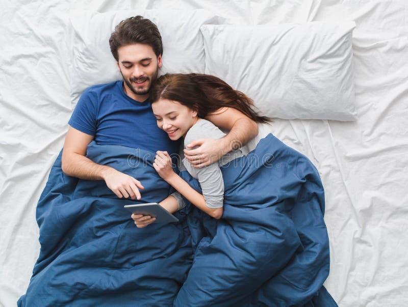 Pares novos no filme de observação do conceito da manhã da opinião superior da cama na tabuleta digital fotografia de stock royalty free