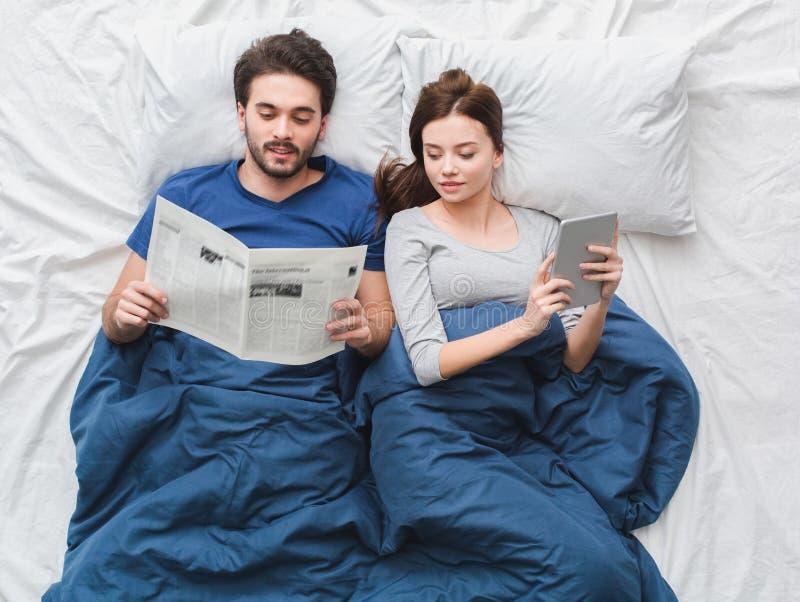 Pares novos no jornal da leitura do indivíduo do conceito da manhã da opinião superior da cama quando menina que usa a tabuleta d imagens de stock royalty free