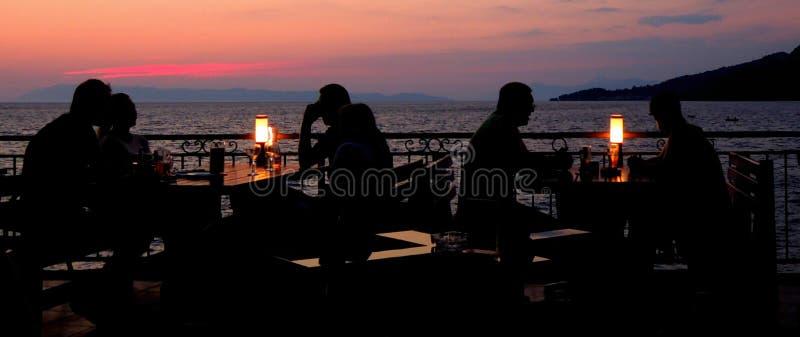 Pares novos no restaurante que tem o jantar Silhueta fotografia de stock