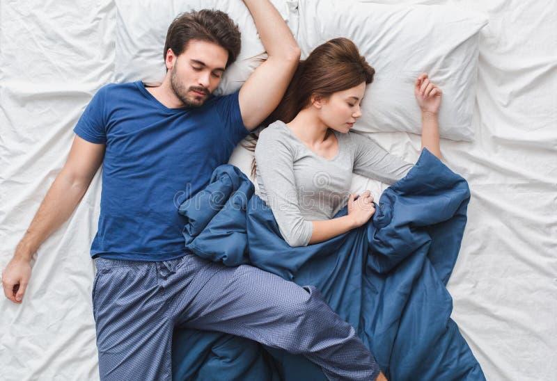 Pares novos no sono do conceito da manhã da opinião superior da cama relaxado fotografia de stock