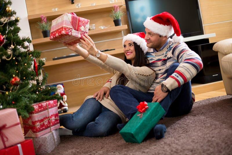 Pares novos nos chapéus do Natal que guardam presentes imagens de stock