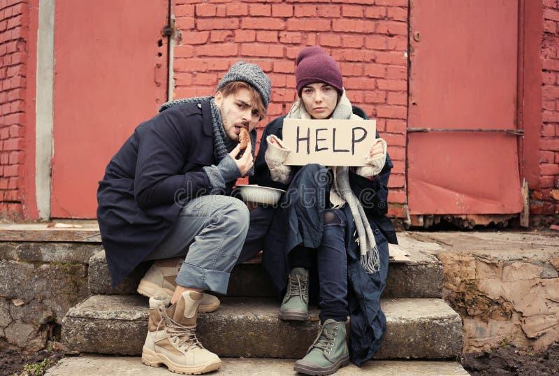Pares novos pobres com sinal da AJUDA e pão na rua imagens de stock royalty free