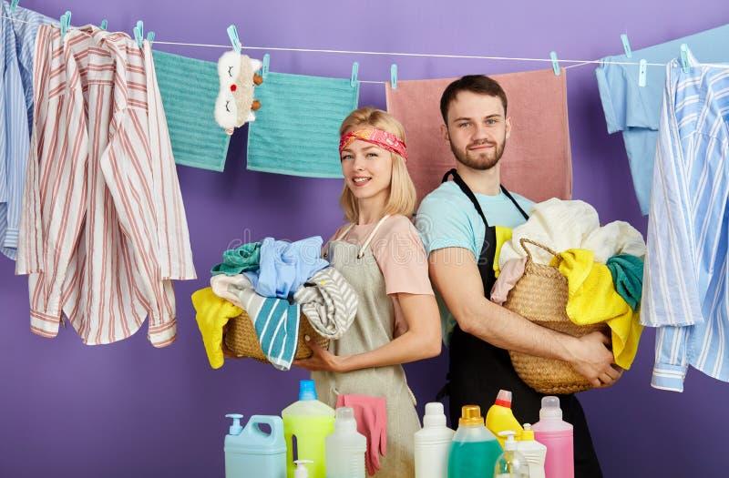 Pares novos positivos com as cestas completas da roupa suja imagem de stock royalty free