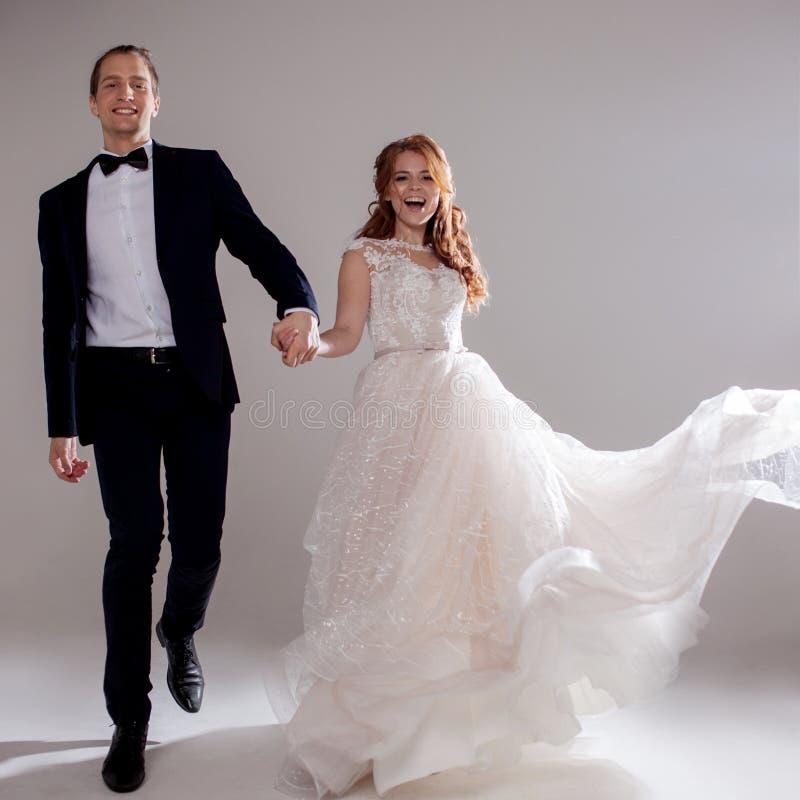 Pares novos positivos que riem e que dançam junto Os pares no estúdio um fundo claro fotografia de stock royalty free