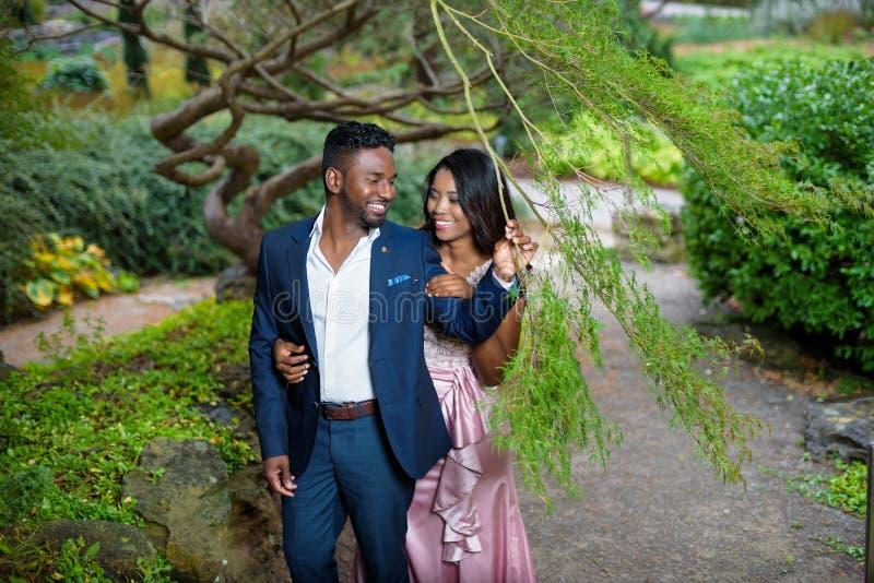 Pares novos que abraçam e que sorriem ao apreciar um jardim bonito imagens de stock royalty free
