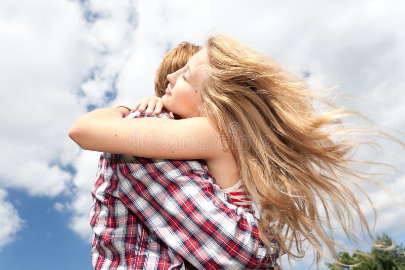 Pares novos que abraçam no dia ensolarado fotografia de stock