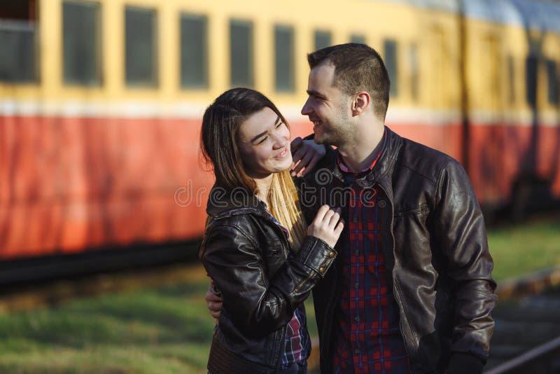 Pares novos que abraçam no fundo de um trem de passagem fotos de stock