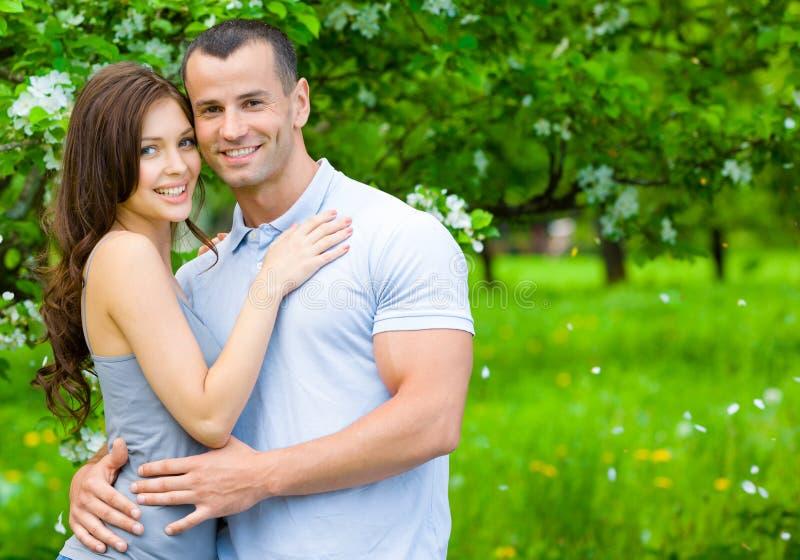 Pares novos que abraçam perto da árvore florescida imagens de stock