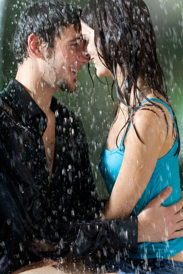 Pares novos que abraçam sob uma chuva imagens de stock