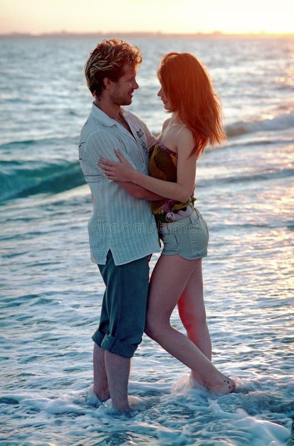 Pares novos que amam na praia fotografia de stock royalty free