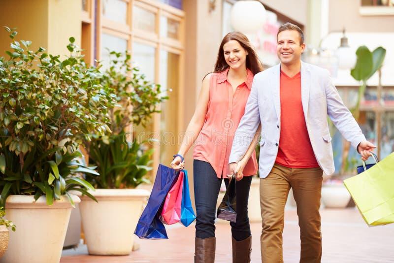 Pares novos que andam através da alameda com sacos de compras foto de stock