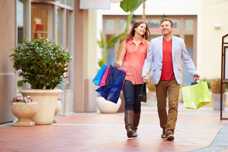 Pares novos que andam através da alameda com sacos de compras imagem de stock royalty free