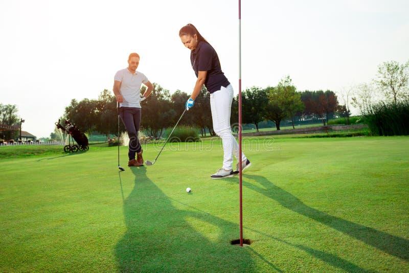 Pares novos que apreciam o tempo em um campo de golfe foto de stock
