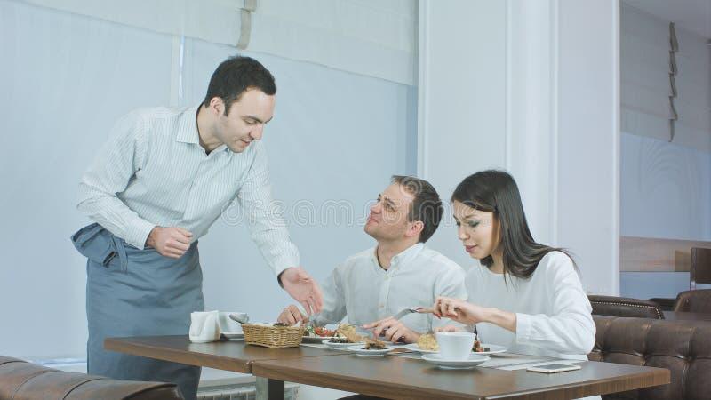 Pares novos que apreciam seu almoço no restaurante quando garçom que traz mais alimento fotografia de stock