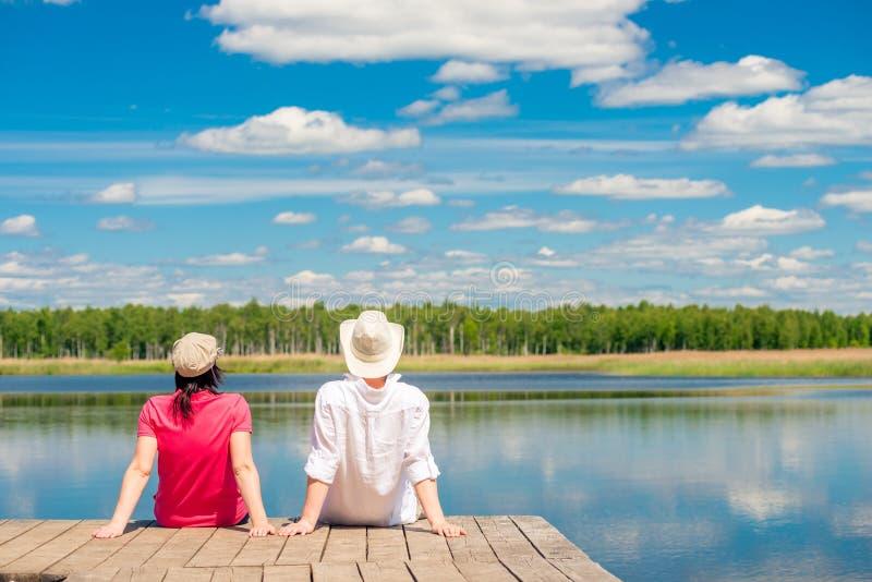 Pares novos que apreciam um assento bonito do lago fotografia de stock royalty free