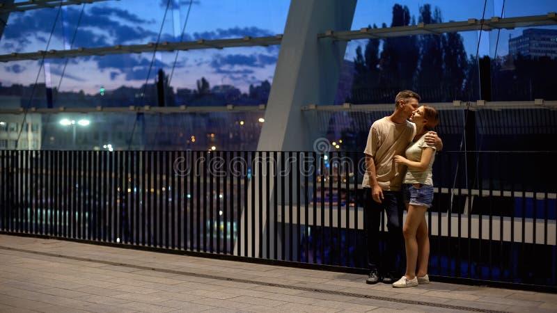 Pares novos que beijam e que abraçam na noite do verão, sentimentos românticos, amor fotos de stock
