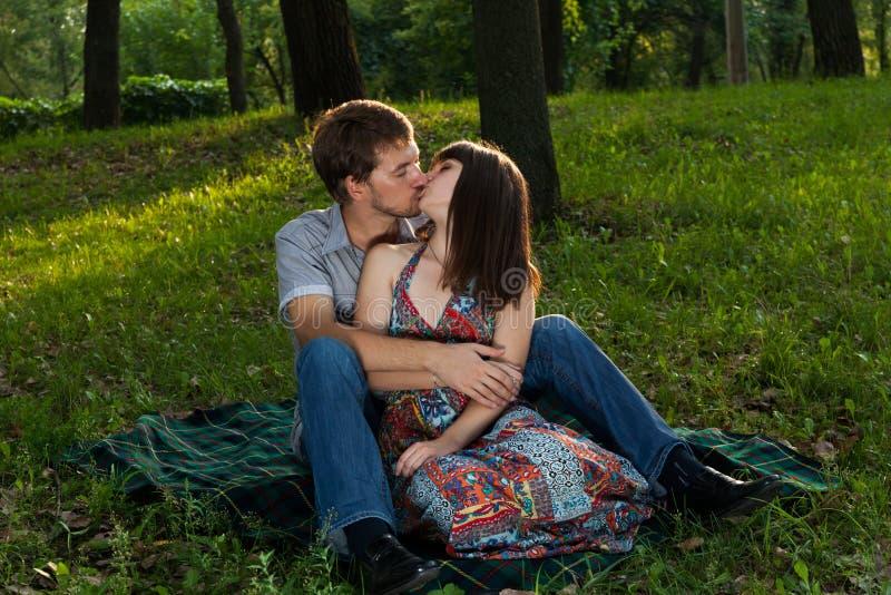 Pares novos que beijam em um piquenique romântico imagens de stock royalty free