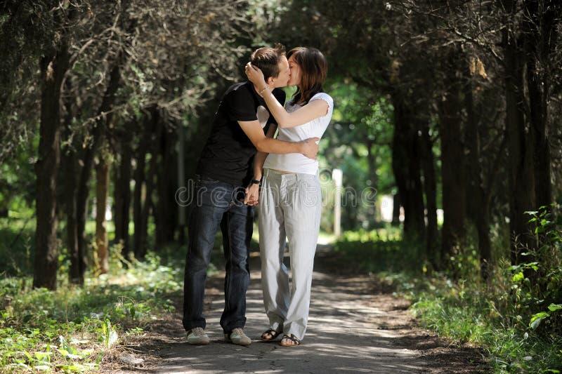 Pares novos que beijam na aléia