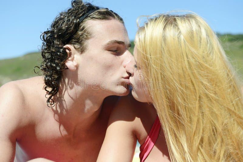 Pares novos que beijam na praia foto de stock
