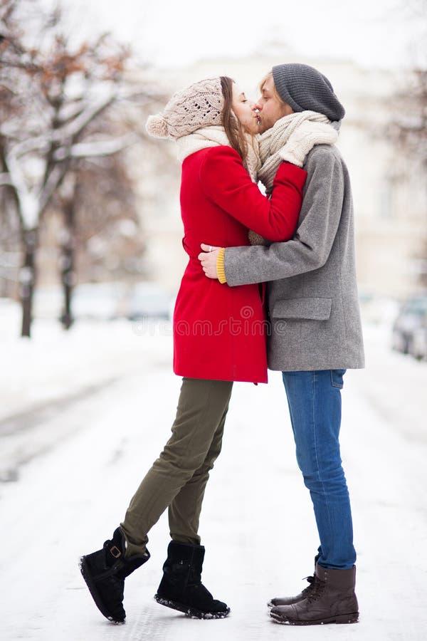 Pares novos que beijam no dia de inverno foto de stock