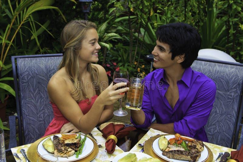 Pares novos que brindam sobre o almoço imagens de stock royalty free